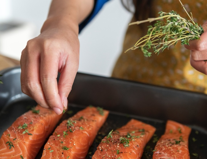 how to get kids to eat fish, woman cooking salmon
